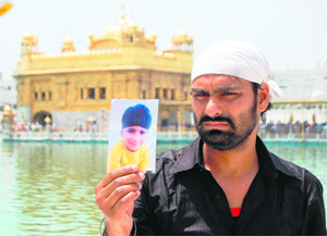 Manjit Singh shows a picture of his son who was kidnapped from the Golden Temple in Amritsar on Saturday. Photo: Sameer Sehgal