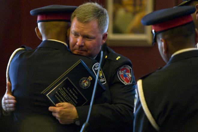Mark Felix Oak Creek police Lt. Brian Murphy hugs a member of the York Regional Police department from Toronto at his retirement ceremony Friday. Murphy was severely wounded in the Sikh Temple shooting last summer.